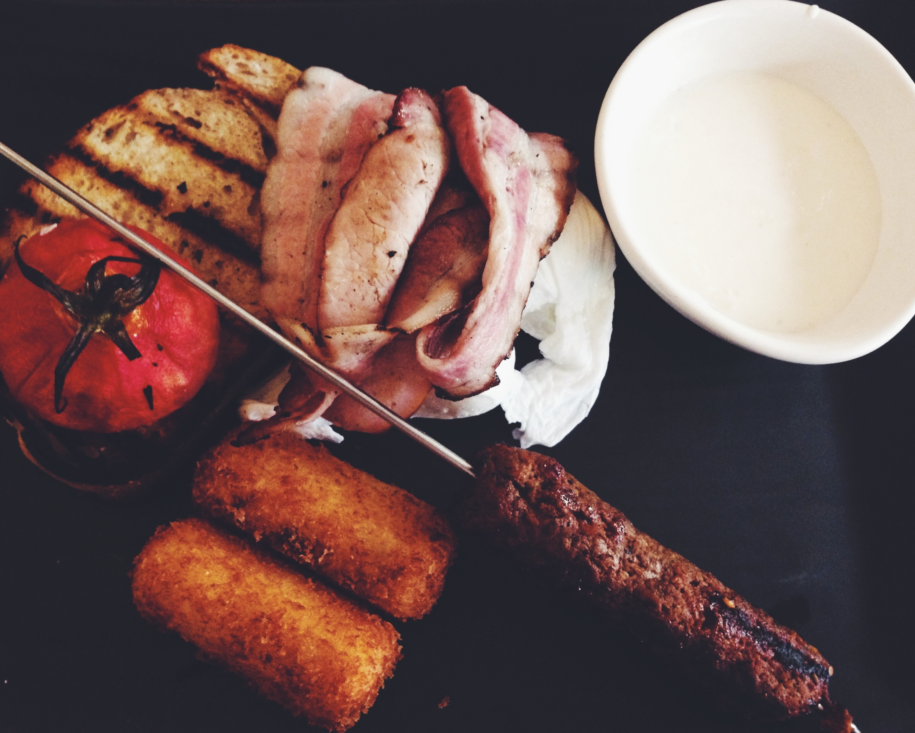 Gerard's big breakfast of double smoked bacon, merguez, confit tomato, kishk yoghurt, eggs  and smoked potato croquette $19