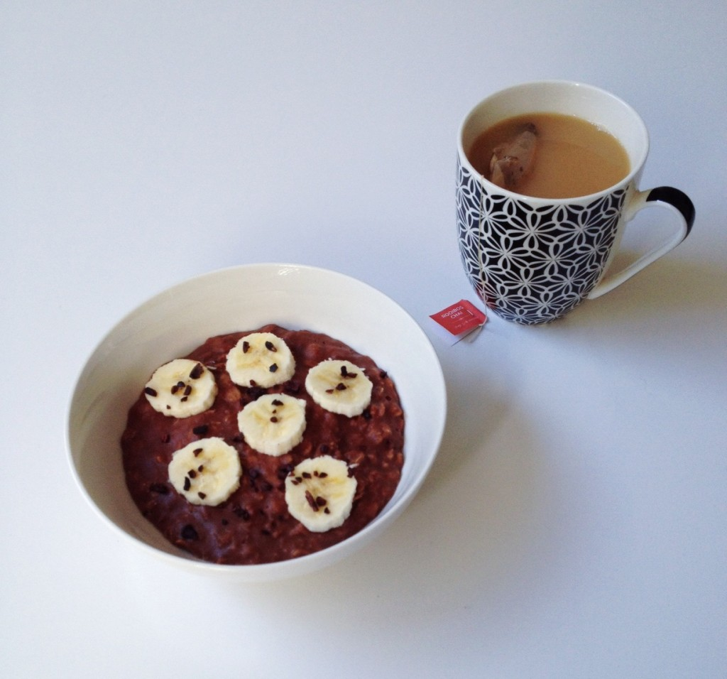 A bowl of chocolate porridge enjoyed with a steaming cup of tea